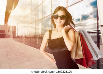 Beautiful happy woman holding shopping bags in her hands