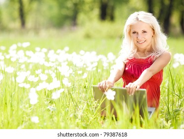 beautiful happy woman with a laptop  in the park  on a warm summer day