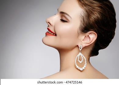 Beautiful happy woman in luxury fashion earrings. Diamond shiny jewelry with brilliants. Sexy retro style portrait. Model with glamour accessories jewelery and bright red lips makeup