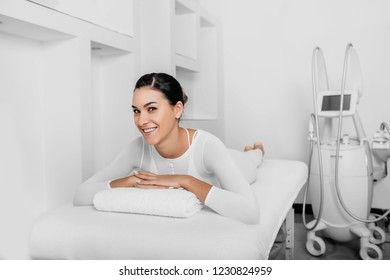 Beautiful happy woman lying on massage table after beauty therapy against cellulite with LPG machine. LPG massage for lifting body