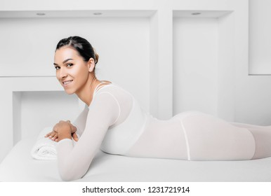 Beautiful happy woman lying on massage table aftertreatment against cellulite with LPG machine. LPG massage for lifting body