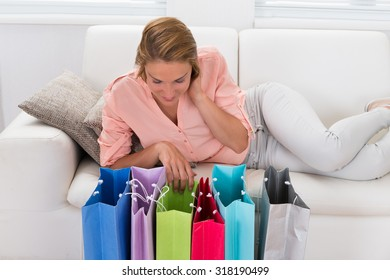 Beautiful Happy Woman On Sofa Looking At Shopping Bags On Wooden Floor