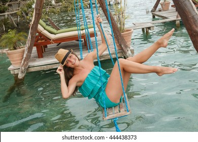 Beautiful and happy woman on the swings which above a water