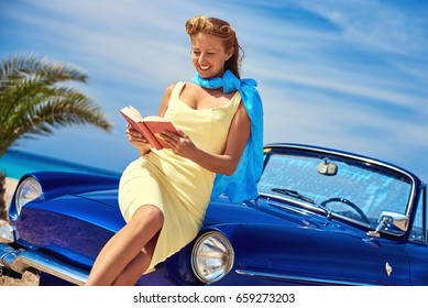 Beautiful happy woman reading a book near retro cabriolet car on the beach. Idyllic scenery