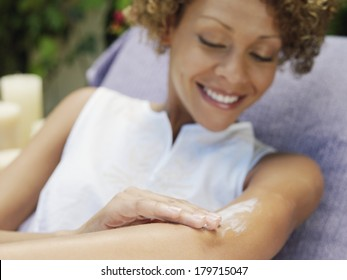Beautiful happy woman relaxing in the garden smiling as she applies sunscreen or skin cream in a skincare and beauty concept