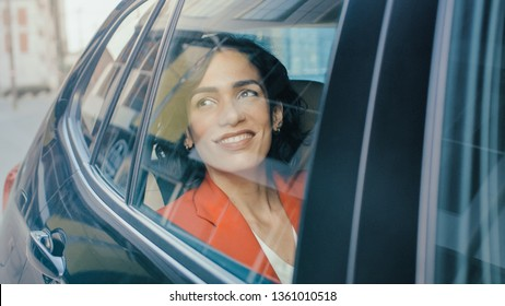 Beautiful Happy Woman Rides on a Passenger Back Seat of a Car, Looks out of the Window in Wonder. Big City View Reflects in the Window. Camera Mounted outside the Car.