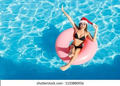Beautiful happy woman in Santa Claus hat with inflatable ring relaxing in blue swimming pool.