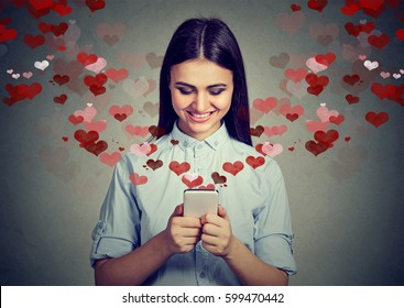 Beautiful happy woman sending love text message on mobile phone with red hearts flying away from screen isolated on gray background. Positive human emotions face expressions