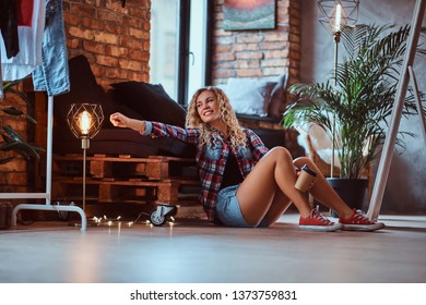 Beautiful happy woman is sitting next to the pallet sofa with cup of coffee. She is wearing hotpants and checkered shirt. Modern loft with brick wall and lamps at background.