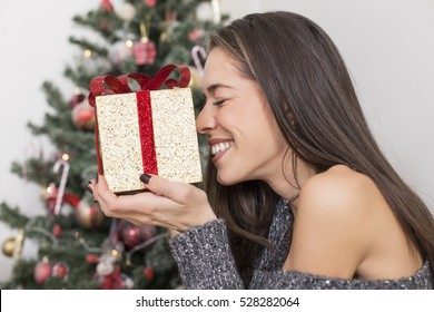 Beautiful happy woman sitting next to Christmas tree with with a gift in her hands