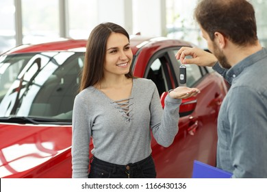 Beautiful and happy woman smiling, looking at man and receiving keys from her new red car. Male manager selling automobile in car dealership to female customer and giving her keys.
