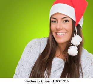Beautiful happy woman wearing a christmas hat against a green background