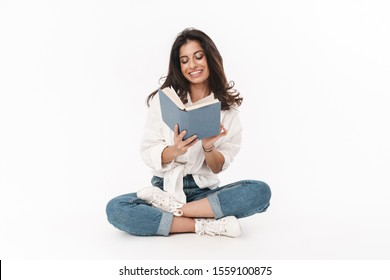 Beautiful happy young brunette woman wearing casual clothing sitting on a floor with legs crossed isolated over white background, reading a book