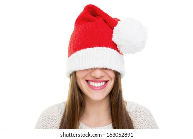 Beautiful happy young Caucasian brunette woman wearing Santa Claus beanie hat that is too big for her. Christmas and teeth care concepts.