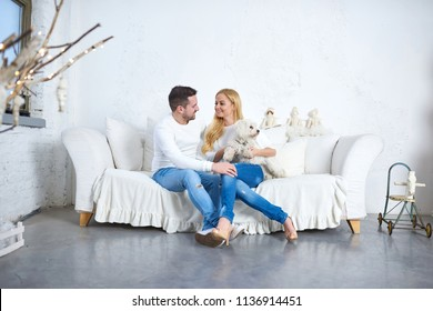A beautiful happy young couple sitting on the sofa with a dog in the living room with christmas decorations.