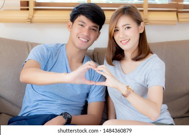 Beautiful happy young couple sitting on sofa fun making gesture heart shape with hand indoor together, man and woman relation feeling love with symbol and sign, lover and romantic concept.