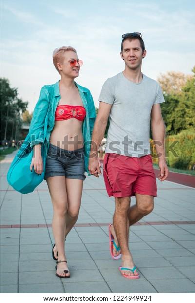 Beautiful happy young couple walking in beachwear holding hands