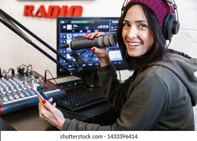 Beautiful happy young female radio host broadcasting in studio, using computer and headphones