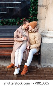 Beautiful happy young funny couple have fun together outdoor on the street in cold winter. Drinking coffee and hugging