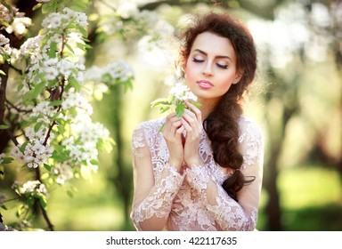 Beautiful happy young girl enjoying the nature. Pretty woman with closed eyes and flower in her hands. Sensual lady with perfect make up and skin in spring blossom garden.Fairy tail and art work.