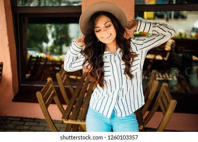 beautiful happy young girl in a hat resting outdoors, woman in cafe