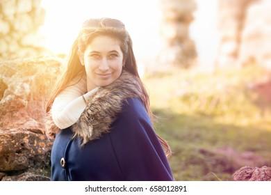 Beautiful happy young girl posing outdoors amongst ruins in beautiful light