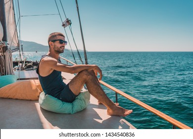 Beautiful happy young man on sea vacation on a boat tour. Male enjoying summer time holiday on sailing boat.