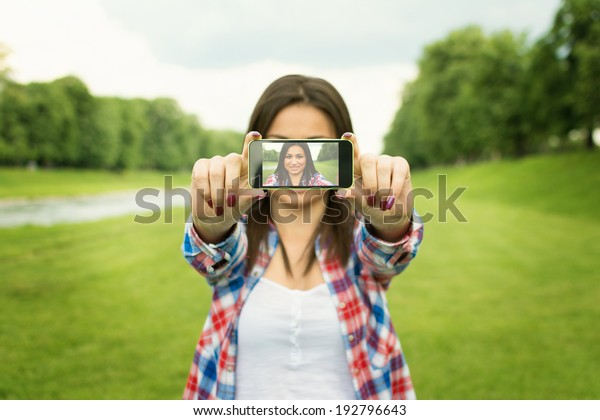 Beautiful happy young mixed race woman taking a selfie photo with smart phone outdoors in park on summer day. Modern millennial youth lifestyle and travel concept.