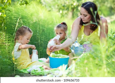 Beautiful and happy young mother eating apple together with her small daughter. Summer park in background