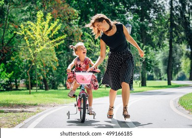 Beautiful and happy young mother teaching her cute daughter to ride a bicycle. Both smiling and looking at each other. Summer park in background
