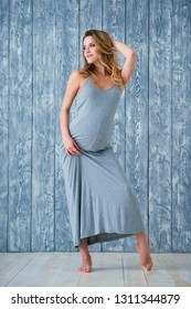 Beautiful happy young pregnant woman with curly blond hair posing dancing near the gray wooden background.