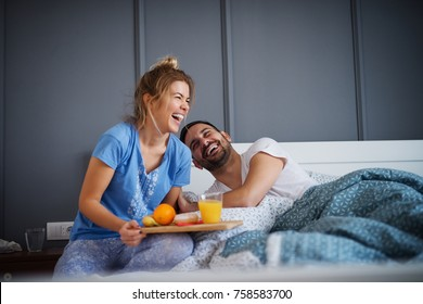 Beautiful happy young romantic girl brings breakfast to her husband in the bed and laughing together after he wakes up.