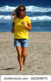 Beautiful happy young smiling woman with loose hair in yellow t-shirt and blue frayed cut-offs runs along the beach away from the sea