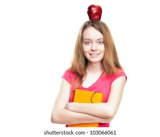 Beautiful and happy young student girl with apple on her head and book in her hands. Looking into the camera. Isolated on white background.