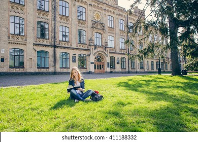 Beautiful, happy young student girl sitting on green grass near the backpack, bag under the tree near the campus, university, school, education. Summer, spring green park