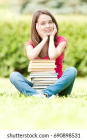 beautiful and happy young student girl sitting on green grass, pile of books under her hands, smiling and looking into the camera. Summer or spring green park in background
