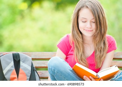 beautiful and happy young student girl sitting on bench, smiling and reading book. Summer or spring green park in background