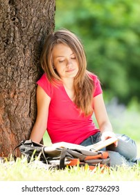 beautiful and happy young student girl sitting on green grass under the tree, smiling and reading book. Summer or spring green park in background