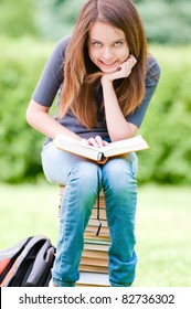 beautiful and happy young student girl sitting on pile of books, holding book in her hands, smiling and looking into the camera. Summer or spring green park in background