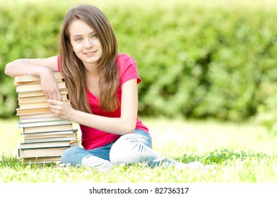 beautiful and happy young student girl sitting on green grass, pile of books under her hand, smiling and looking into the camera. Summer or spring green park in background
