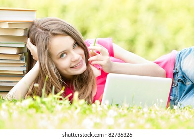 beautiful and happy young student girl lying on grass with laptop computer, smiling and looking into the camera. Pile of books near her head. Summer or spring green park in background