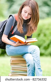 beautiful and happy young student girl sitting on pile of books, holding book in her hands and reading. Backpack on her shoulder. Summer or spring green park in background