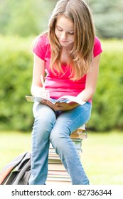 beautiful and happy young student girl sitting on pile of books, holding exercise book in her hands, smiling and writing. Summer or spring green park in background