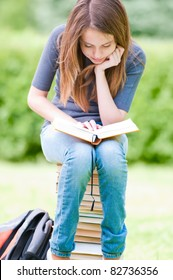 beautiful and happy young student girl sitting on pile of books, holding book in her hands and reading. Summer or spring green park in background