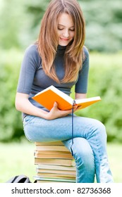 beautiful and happy young student girl sitting on pile of books, holding book in her hands, smiling and reading. Summer or spring green park in background