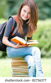 beautiful and happy young student girl sitting on pile of books, holding book in her hands, smiling and looking into the camera. Backpack on her shoulder. Summer or spring green park in background