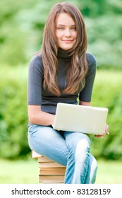 beautiful and happy young student girl sitting on pile of books with laptop computer, smiling and looking into the camera. Summer or spring green park in background