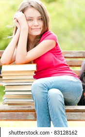 beautiful and happy young student girl sitting on bench, her hands on pile of books, smiling and looking into the camera. Summer or spring green park in background