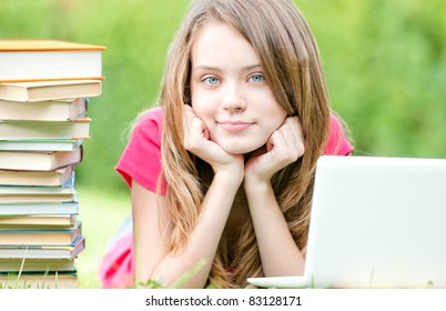 beautiful and happy young student girl lying on grass with laptop computer, smiling and looking into the camera. Pile of books nearby Summer or spring green park in background