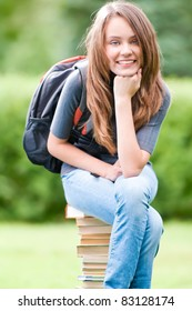 beautiful and happy young student girl sitting on pile of books, smiling and looking into the camera. Backpack on her shoulder. Summer or spring green park in background